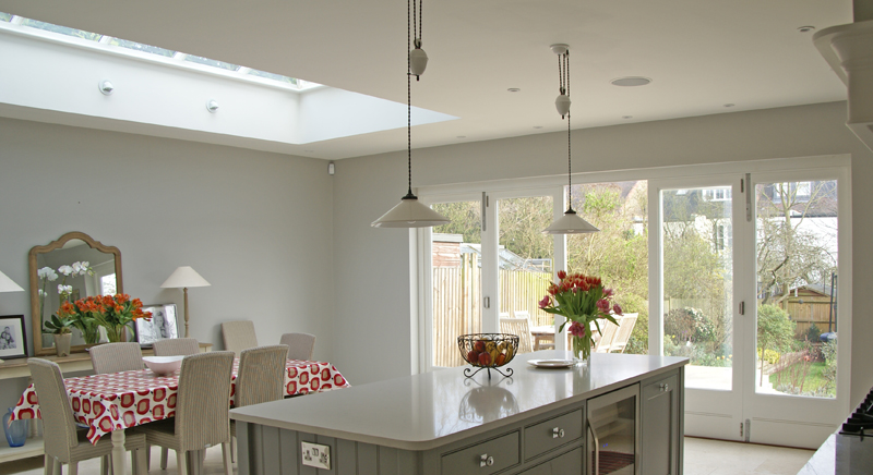 Bespoke rectangular roof lantern sits above a dining area.